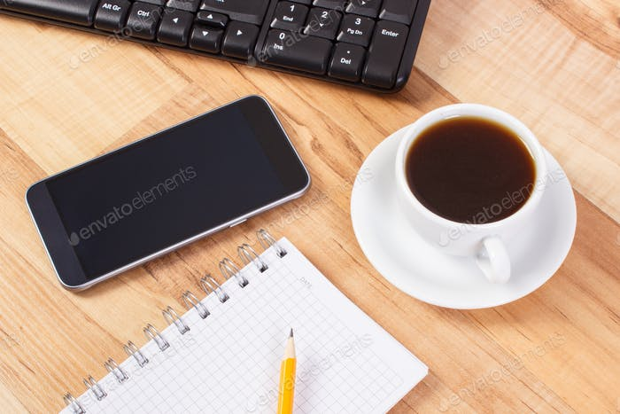 Mobile phone with notepad for writing notes and cup of coffee, using electronics concept