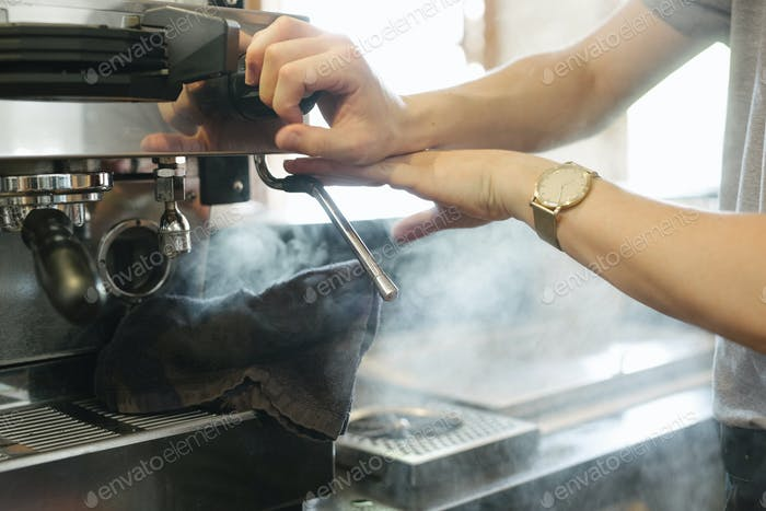 Nahaufnahme von Dampf, der aus einer kommerziell Espressomaschine kommt.