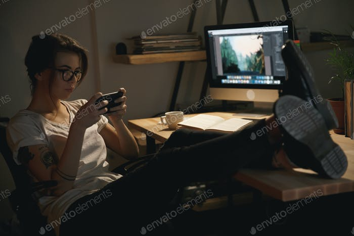 Young lady designer indoors at night play games by phone