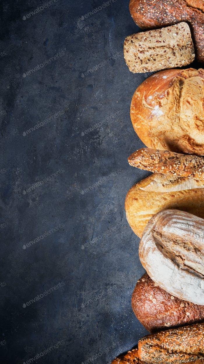 Banner Assortment of baked bread on dark surface