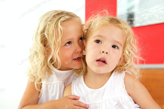 Two cute little girls together at home