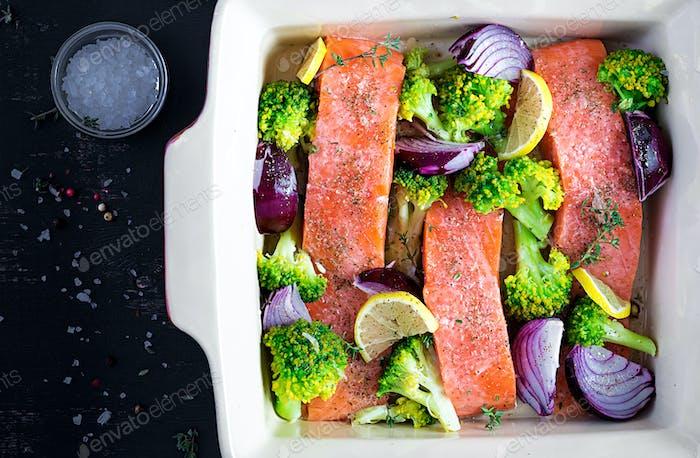 Lachs, Brokkoli und rote Zwiebelscheiben werden in einer Auflaufform zubereitet. Draufsicht, Overhead
