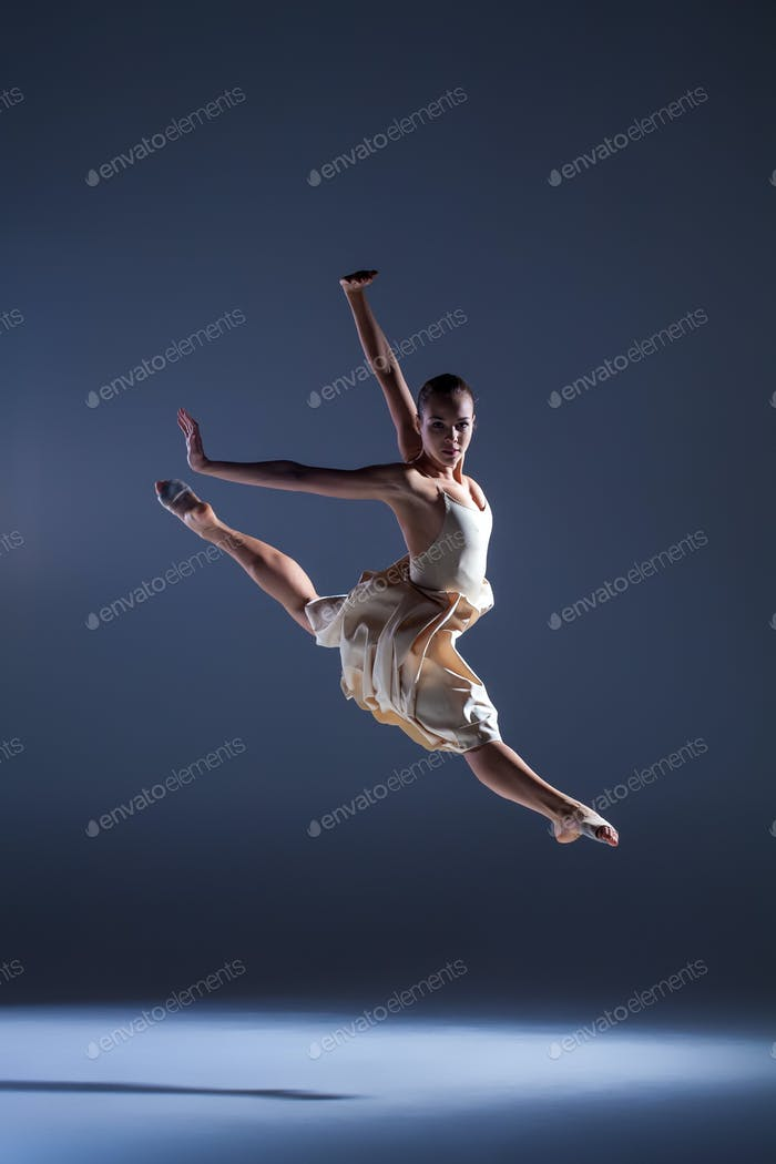 Young beautiful dancer in beige dress jumping on gray background