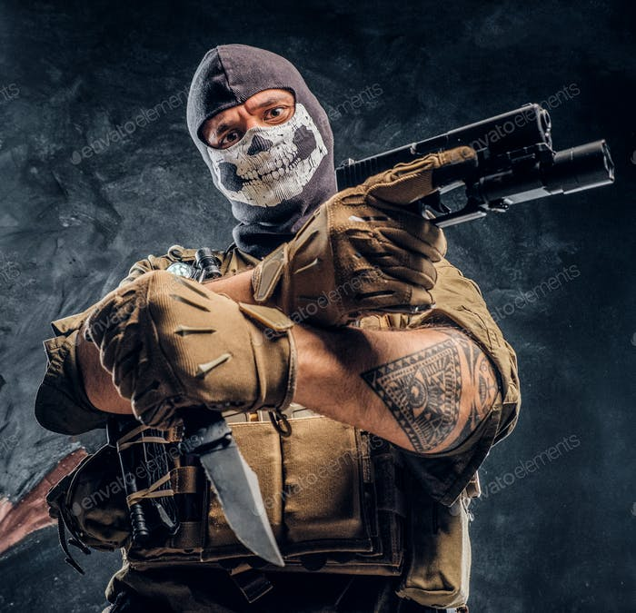 Terrorist in a military uniform and a skull balaclava holding a pistol and a knife
