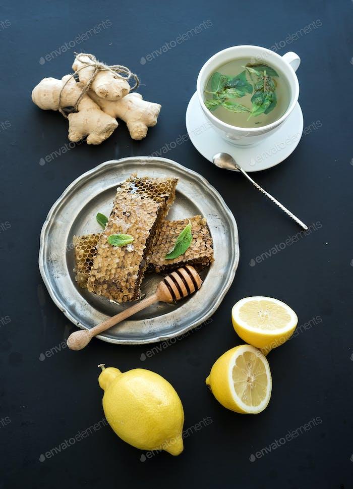Tasse Kräutertee mit frischer Minze, Honig, Zitrone, Ingwer auf grunge schwarzem Hintergrund