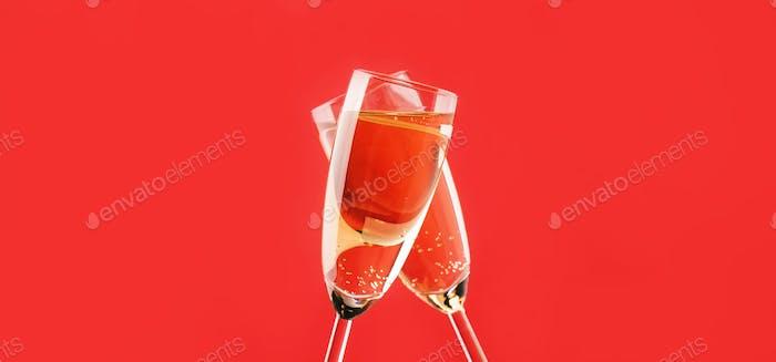 Zwei Champagnerflöten machen Beifall auf Rotlicht Bokeh Hintergrund Banner