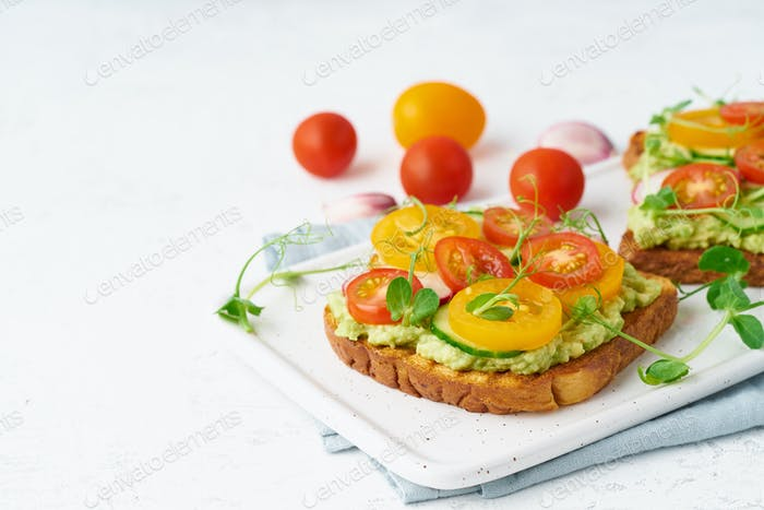 avocado toast with cherry tomatoes and herbs, breakfast, closeup, copy space