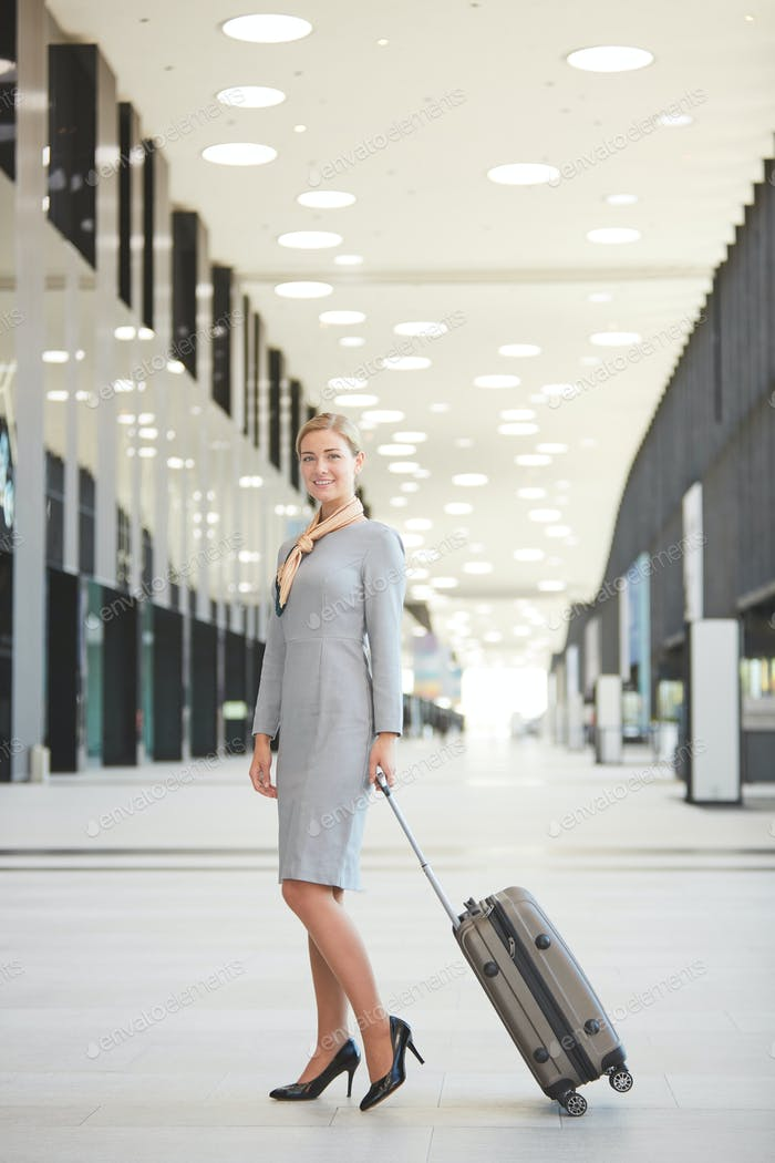 Elegant Woman with Suitcase in Airport