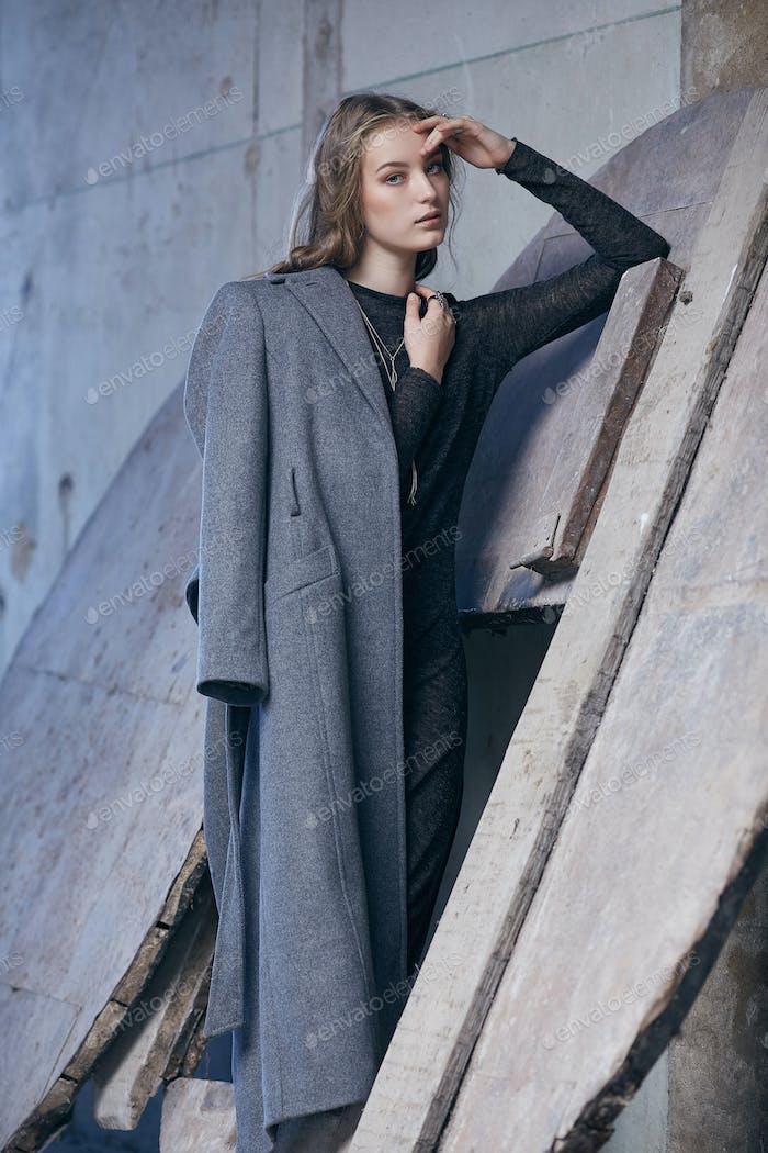 Eine Dame in einer langen grauen Jacke.