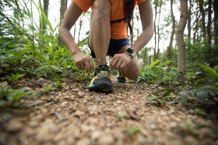 Ultramarathon runner tying shoelace in rainforest