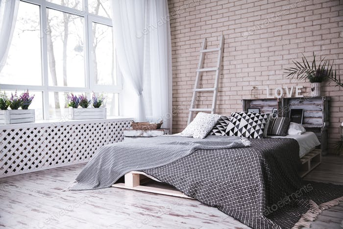 Modern bedroom with comfortable double bed and stylish white brick wall