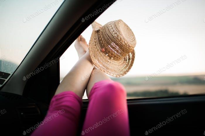 Beine, die aus dem Autofenster herausragen