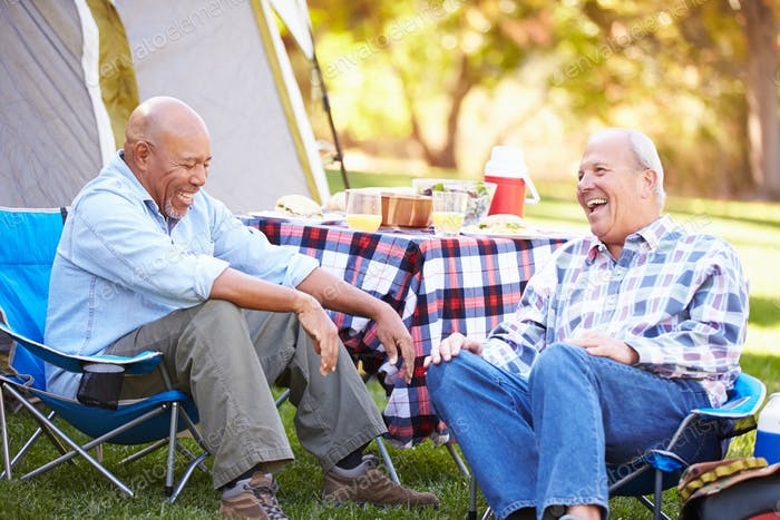 Two Senior Men Relaxing On Camping Holiday