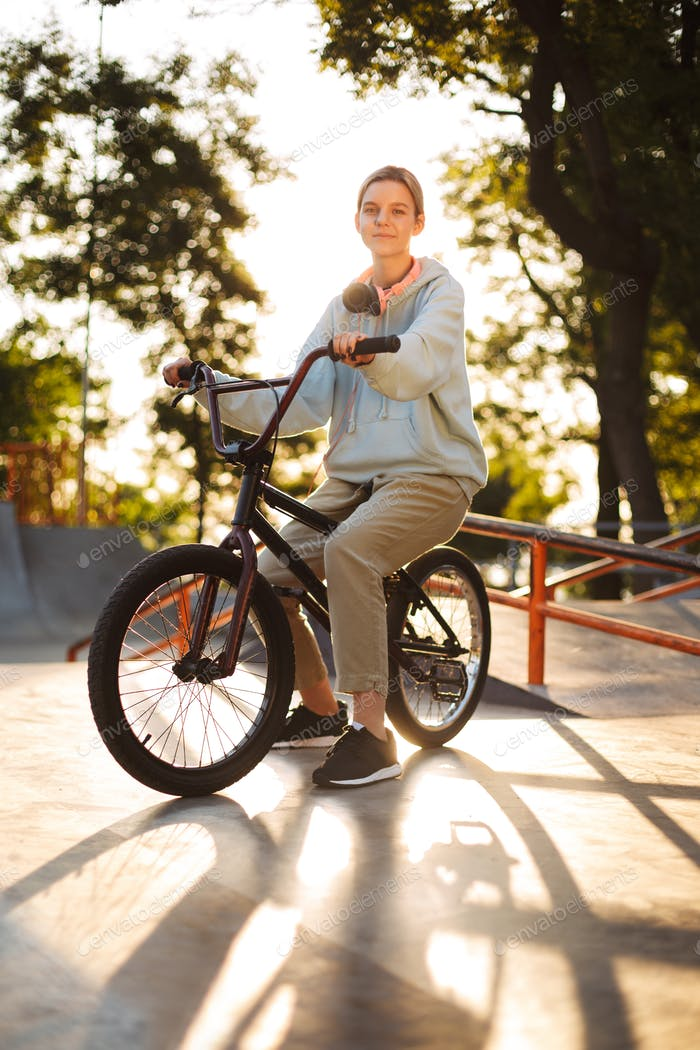 Beautiful smiling girl with headphones on bicycle dreamily looki