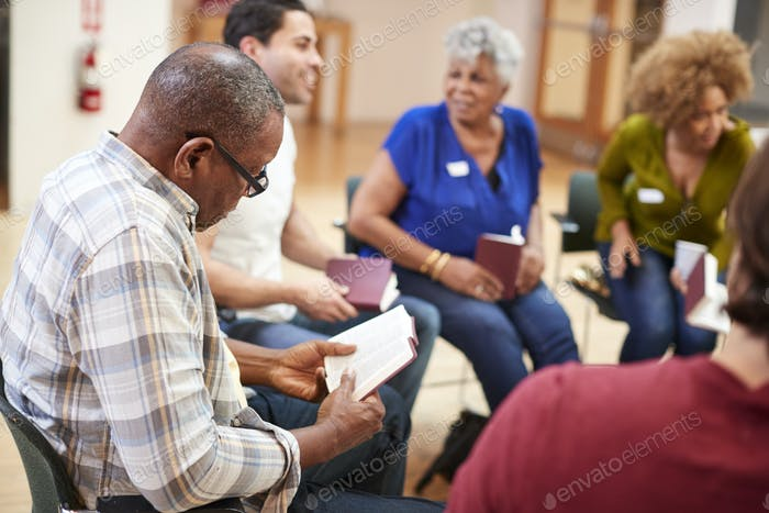 People Attending Bible Study Or Book Group Meeting In Community Center