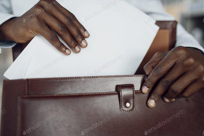 Schwarzer Geschäftsmann hält Aktentasche im Auto-Showroom