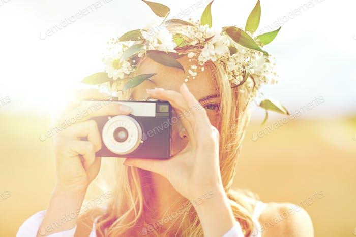 glückliche Frau mit Filmkamera im Blumenkranz