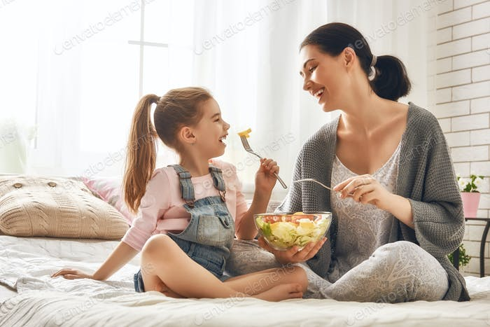 Mother and daughter eating salad