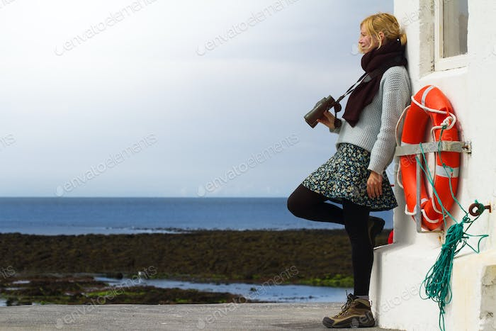 Beautiful woman with binoculars by the lighthouse