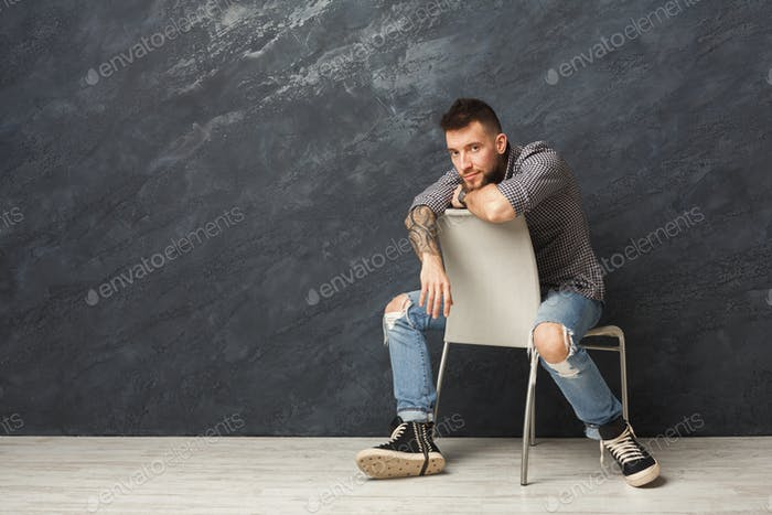 Handsome man sitting on the chair and posing in studio