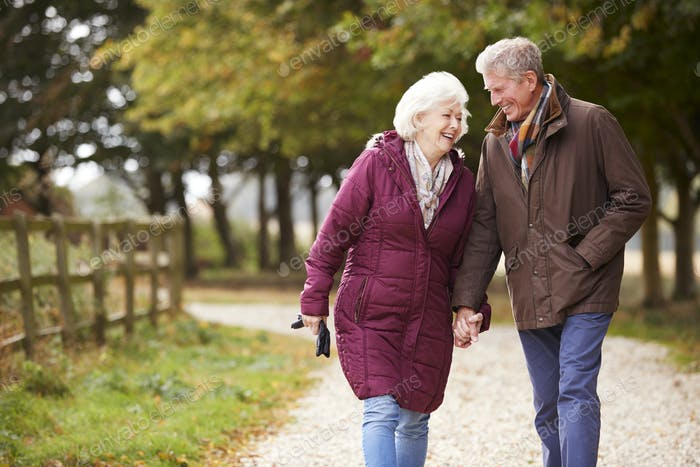Active Senior Couple On Autumn Walk On Path Through Countryside