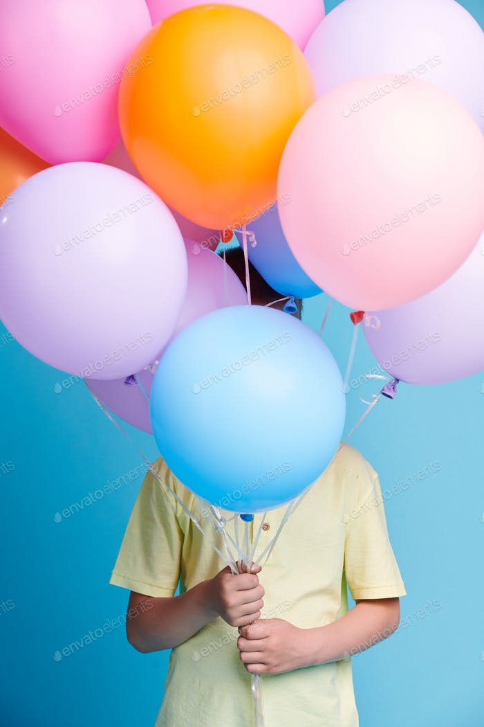 Little child in yellow shirt hiding behind bunch of birthday balloons