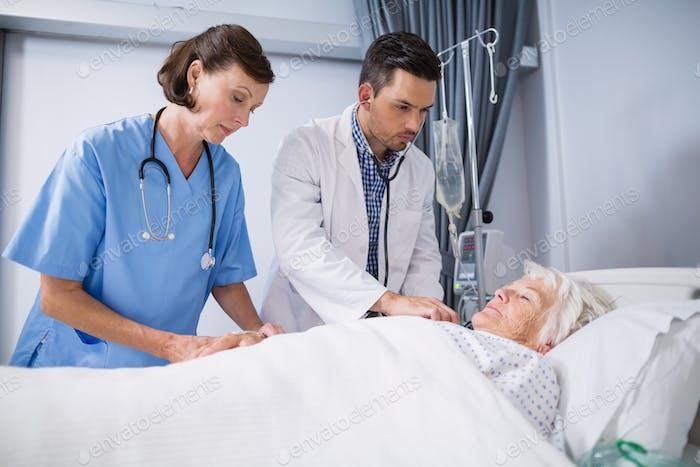 Doctors examining senior patient with stethoscope