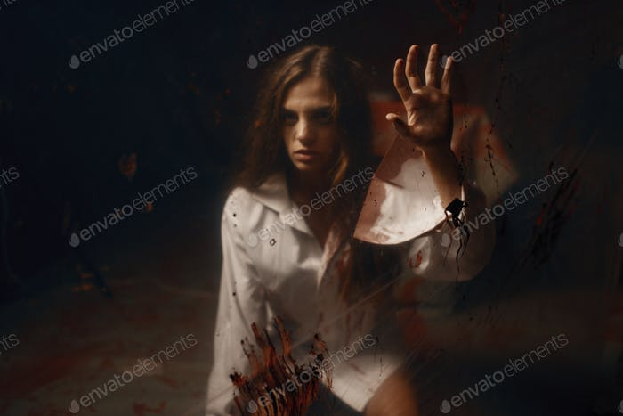 Victim with with bloody hands in hospital basement