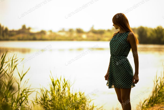 Young woman standing and enjoying summer day with lake at background
