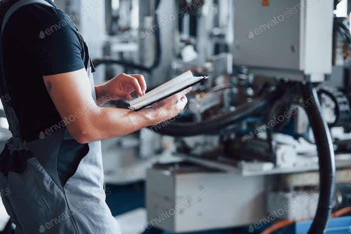 Turns the page of notepad. Industrial worker indoors in factory. Young technician
