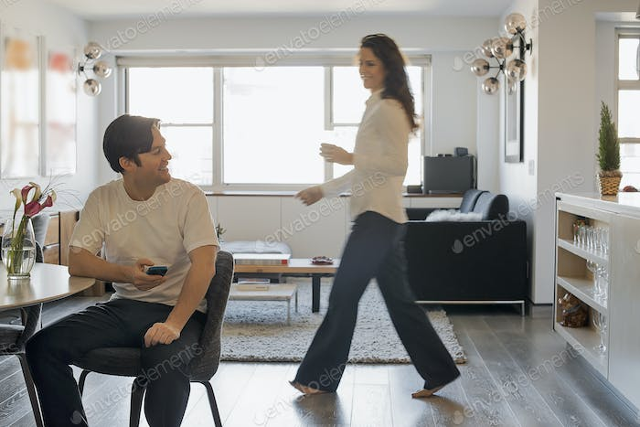 Couple at Home, Man using smartphone, Woman walking past