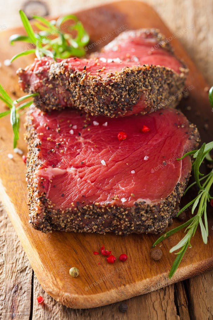 raw beef steak with spices and rosemary on wooden background