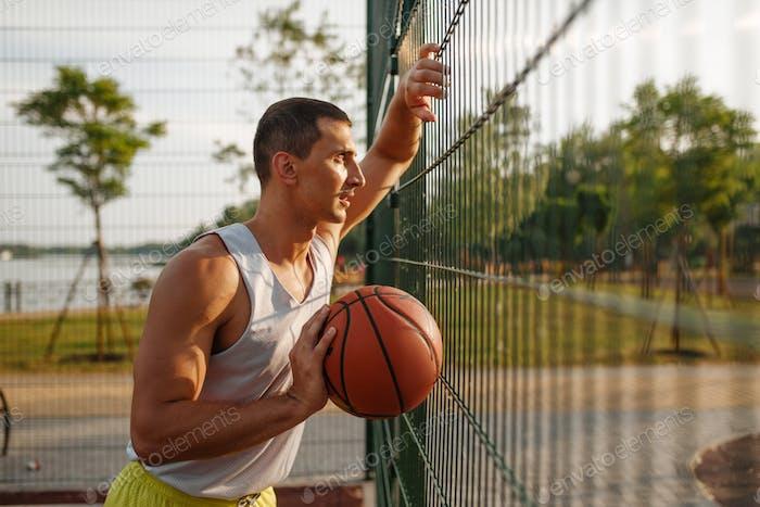 Jugador de baloncesto de pie en la valla de malla