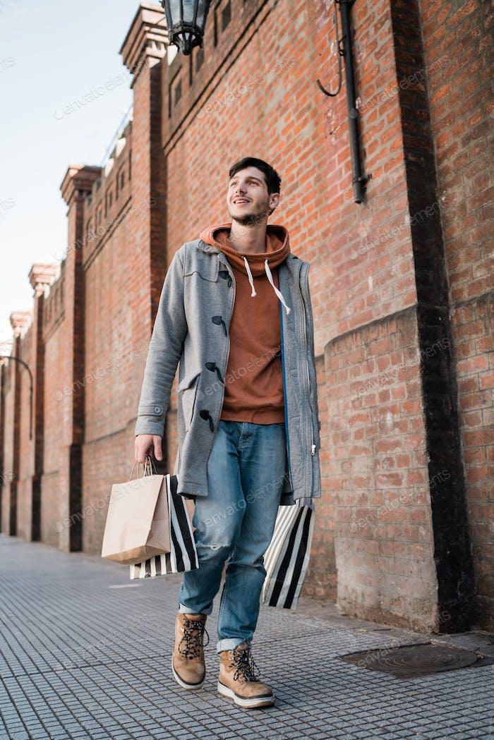 Junger Mann hält Einkaufstaschen während des Spaziergangs auf der Straße.