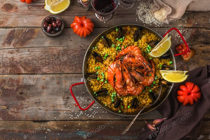 Large pan of paella with seafood and vegetables, copy space