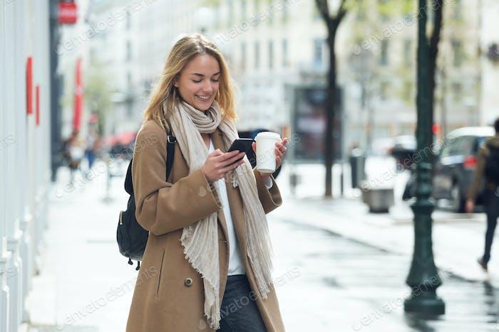 bastante joven mujer el uso de su teléfono móvil mientras la celebración de taza de c