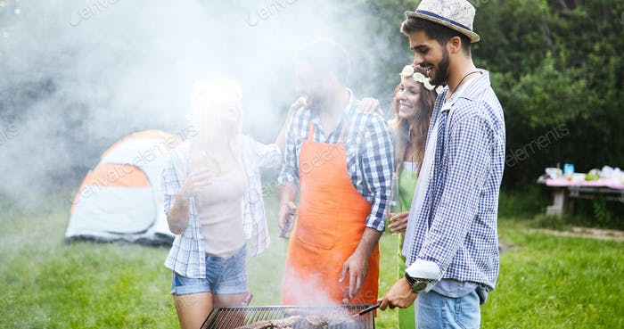 Friends making barbecue and having lunch