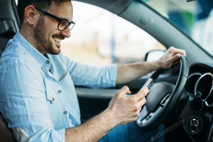 Hombre guapo que utiliza el sistema de navegación durante la conducción del coche