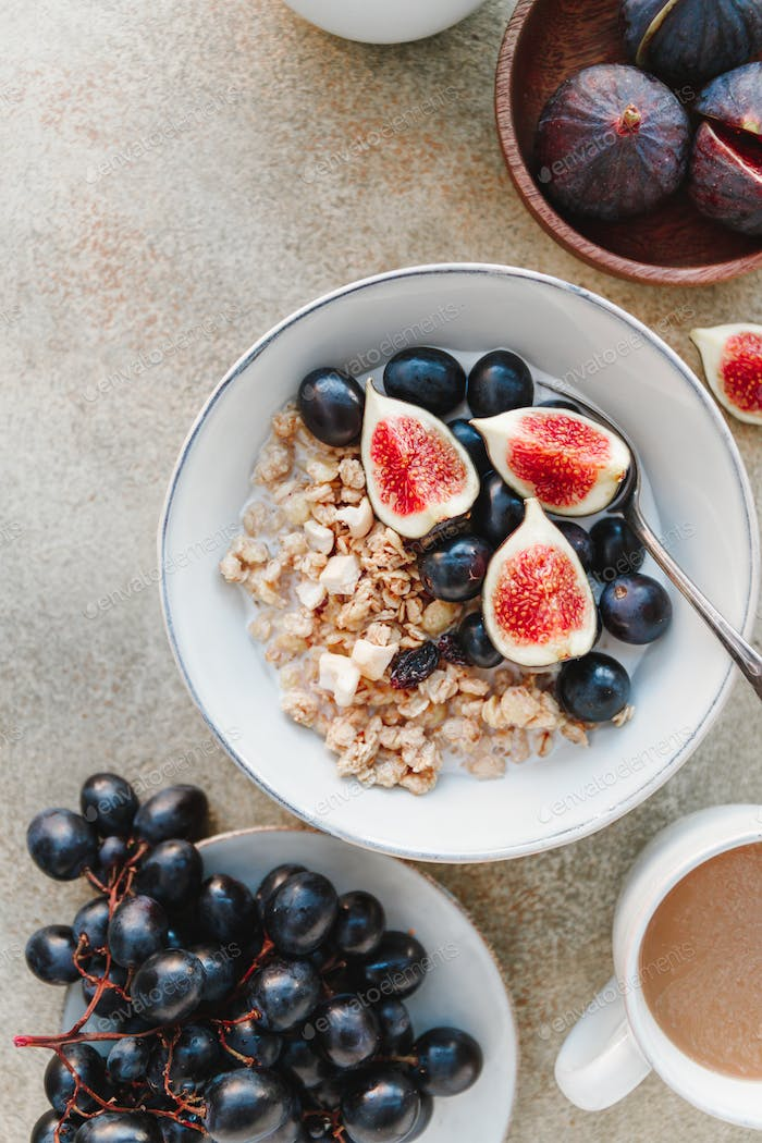 Top view of a breakfast bowl with granola, blue grape and fig slices
