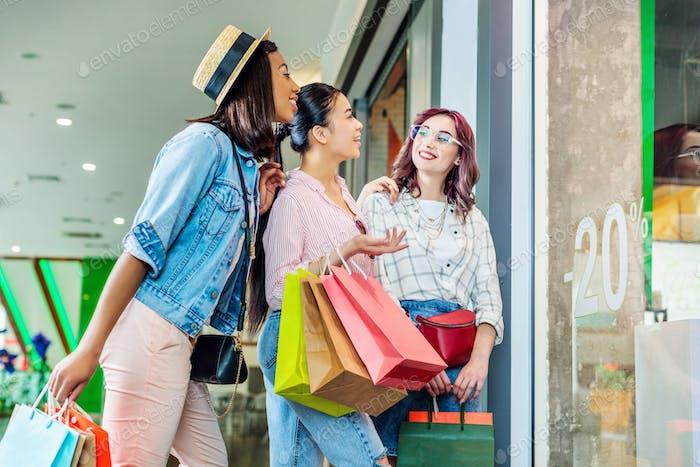 multikulturelle Hipster Mädchen mit Einkaufstaschen im Einkaufszentrum, Freunde Shopping-Konzept