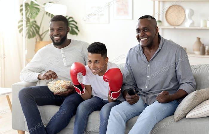 Schwarzer Vater, Sohn und Großvater beobachten Boxen Spiel Im Fernsehen Und Jubel