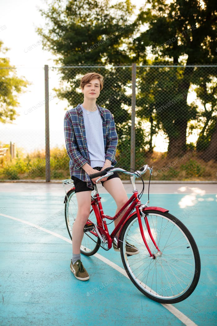 Portrait of boy that thoughtfully looking in camera while standing with classic bicycle