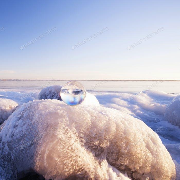 Glass sphere on frozen rock formations
