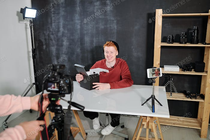 Cheerful male vlogger by desk going to unpack box with new photocamera