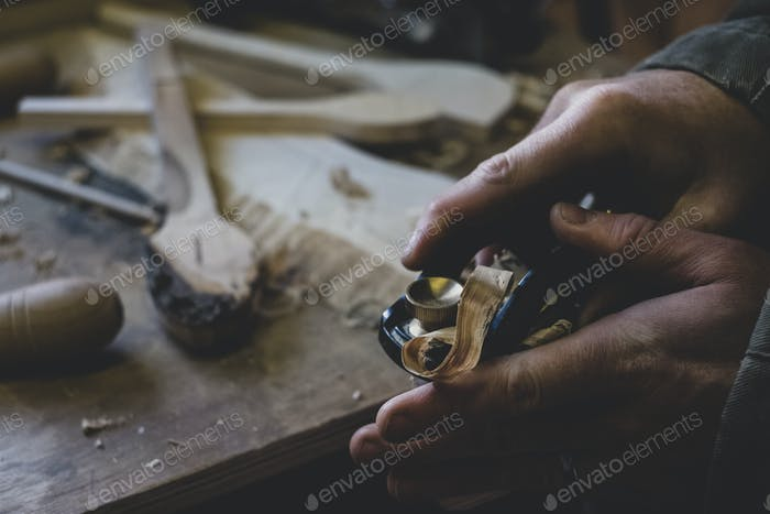 High angle close up of man using plane on piece of wood.