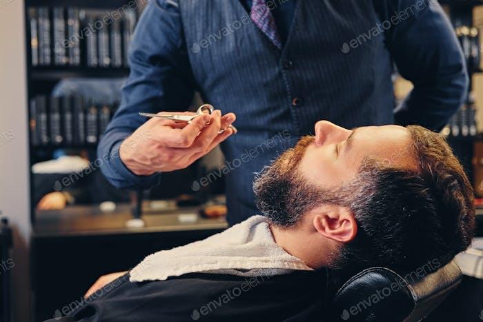 Стильный парикмахер ухаживает за бороду мужчины в салуне.