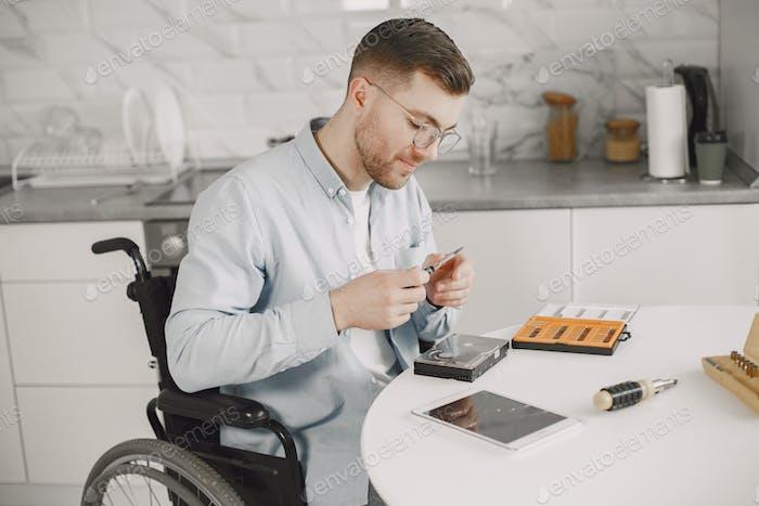 Joven hombre discapacitado reparando la placa base en la cocina