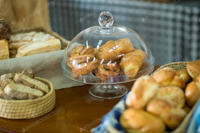 Close-up of croissants on cake stand at counter