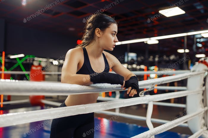 Woman in boxing bandages at the ropes on ring