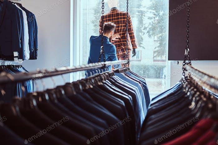 Стильный бородатый продавец заботится о костюме на манекене в магазине мужской одежды.